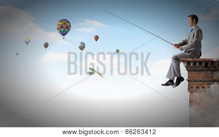 Businessman sitting on top of building and fishing with rod