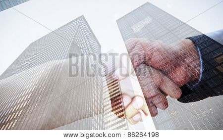 Close up on partners shaking hands against skyscraper