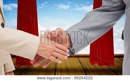 Close up of business people shaking their hands against stage with red curtains