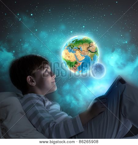 Boy sitting in bed and dreaming. Elements of this image are furnished by NASA