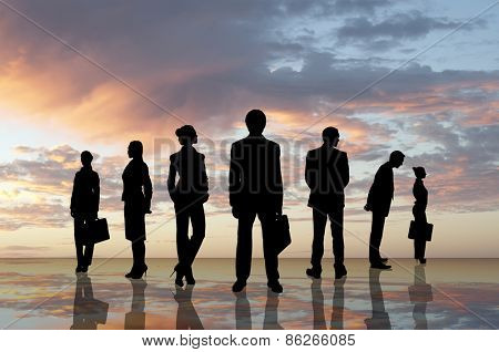 Silhouettes of business people against sunset landscape