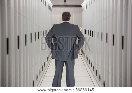 Businessman standing back to the camera with hands on hip against data center