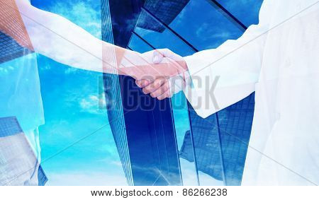Mid section of a doctor and patient shaking hands against skyscraper