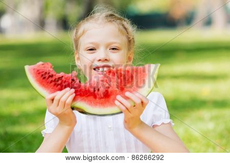 Cute girl in park eating juicy watermelon