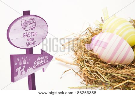 Easter egg hunt sign against two easter eggs in straw