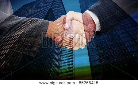 Handshake between two business people against low angle view of skyscrapers