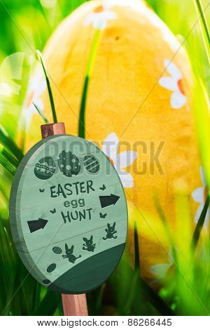 Easter egg hunt sign against easter egg nestled in the green grass