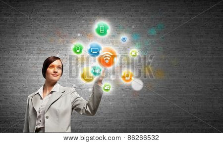 Young attractive businesswoman touching media colorful icon