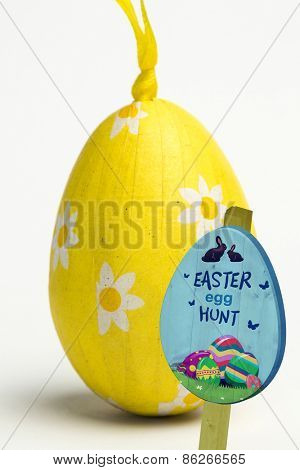 Easter egg hunt sign against yellow wrapped easter egg
