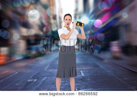 Astonished elegant businesswoman holding binoculars against blurry new york street