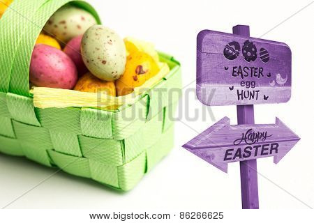 Easter egg hunt sign against speckled easter eggs in a basket