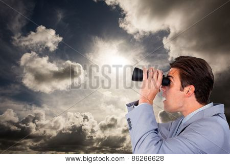 Visionary businessman looking to the future against dark sky with white clouds