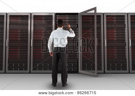 Businessman standing back to the camera pointing against server towers