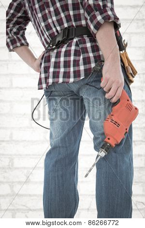 Male handyman holding drill machine against white wall