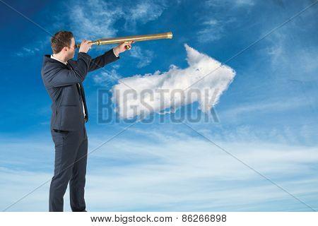 Businessman looking through telescope against cloud arrow