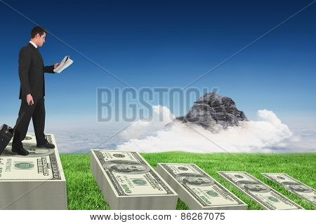 Businessman pulling his suitcase holding newspaper against clouds over mountain peak