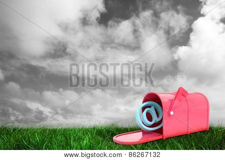 Red email post box against green grass under grey sky