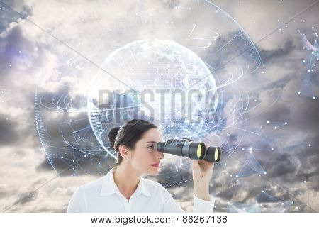 Business woman looking through binoculars against global technology background in blue