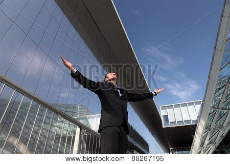 Businessman With Open Arms To The Sky
