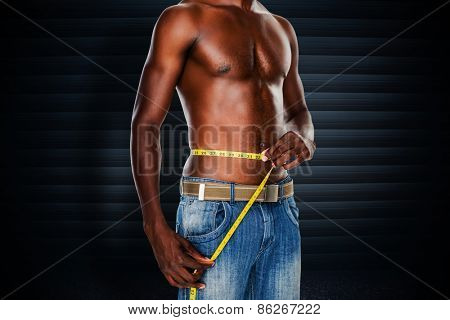 Mid section of a fit shirtless man measuring waist against black background