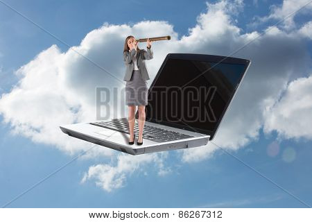 Businesswoman looking through a telescope against cloudy sky