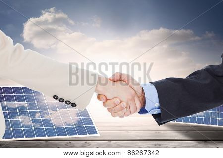 Smiling business people shaking hands while looking at the camera against solar panels on floorboards in the sky