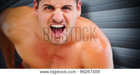 Bodybuilder shouting against grey shutters