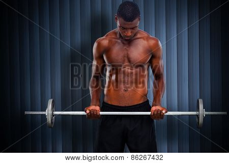 Fit man lifting barbell against grey shutters