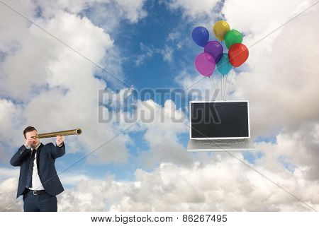 Businessman looking through telescope against blue sky with white clouds