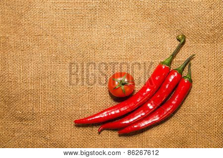 Three Chile Peppers And Cherry Tomat  On Very Old Cloth