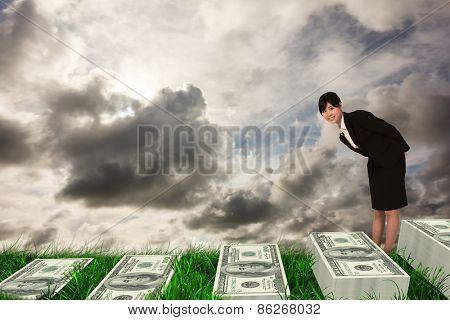 Smiling businesswoman bending against green grass under grey sky