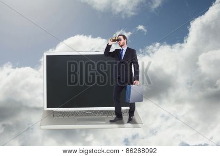 Businessman looking through binoculars holding briefcase against blue sky with clouds