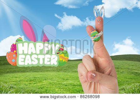 Fingers as easter bunny against field and sky