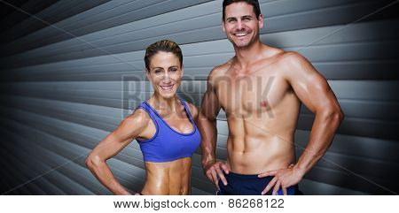 Bodybuilding couple against grey shutters