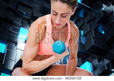 Strong woman doing bicep curl with blue dumbbell against blue and black tile design