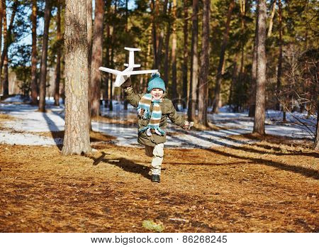 Cheerful boy running with toy airplane