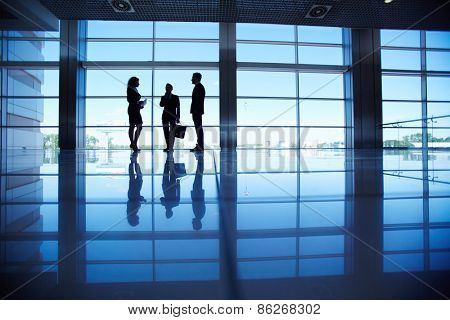Silhouettes of group of office workers standing by the window and talking