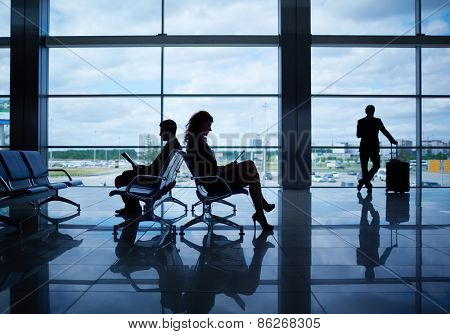 Outline of businesspeople reading in departure lounge