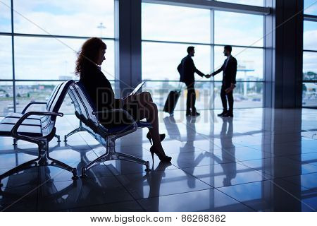 Young woman with touchpad waiting for departure on background of handshaking business partners
