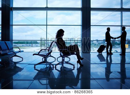 Outline of businesswoman with touchpad sitting in departure lounge on background of handshaking men