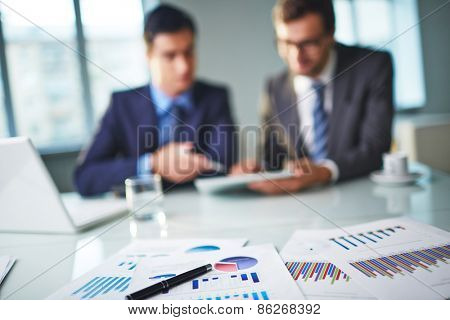 Business documents at workplace and two businessmen networking on background