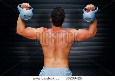 Bodybuilder holding kettlebell against black background