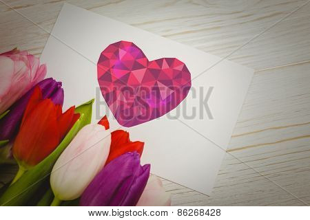 heart against tulips with card