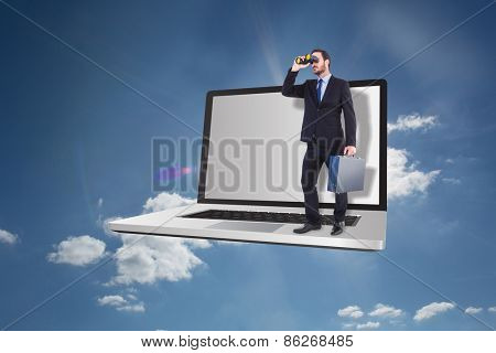 Businessman looking through binoculars holding briefcase against cloudy sky with sunshine