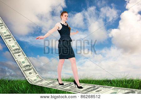 Businesswoman doing a balancing act against green grass under blue sky