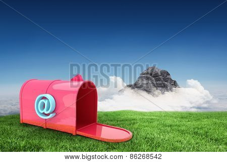 Red email post box against clouds over mountain peak