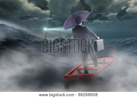 Businessman in boat with umbrella against stormy sea with lighthouse