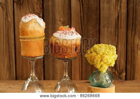 Kulich, Russian Easter Yeast Sweet Breads Decorated With Icing With Yellow Flowers On Wooden Backgro