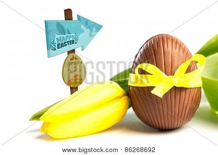 Easter egg hunt sign against chocolate easter egg in a yellow ribbon with tulip