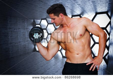 Bodybuilder lifting dumbbell against hexagon room